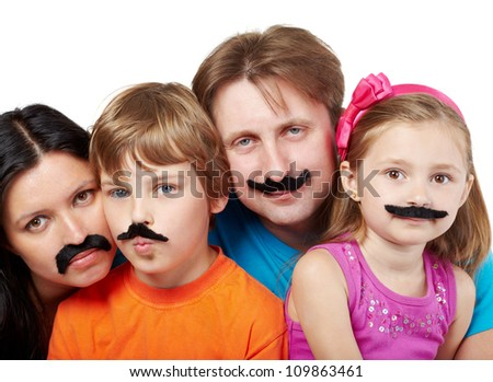 Family of four with glued artificial mustaches, mother and son are serious, father and daughter smile. - stock photo