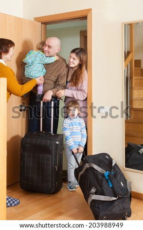 Family of four with luggage coming to grandmother  home - stock photo