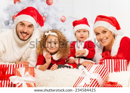 Family of four with presents and Christmas tree - stock photo