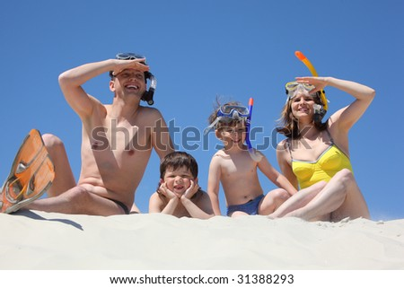 family of four with snorkeling masks sitting on sand and looking afar