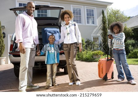 Family of four with suitcases by back of car, smiling, portrait, low angle view - stock photo