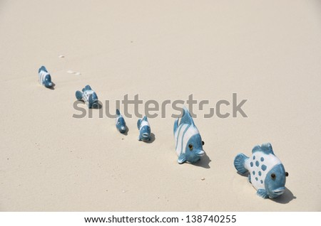 Family of funny fishes on the sandy beach - stock photo