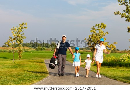 Family of golf players walking at the course - stock photo