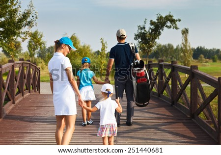 Family of golf players walking in the golf club - stock photo