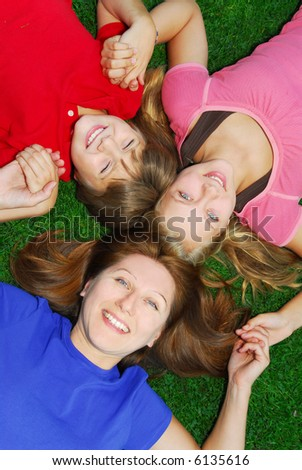 Family of happy mother and children relaxing on green grass - stock photo