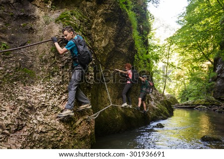 Family of hikers climbing on safety cables in a gorge above the river