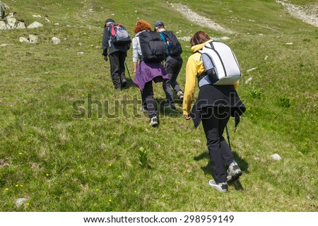 Family of hikers walking on a trail into the mountains - stock photo