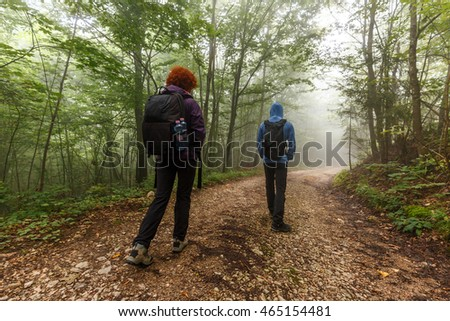 Family of hikers with backpacks walking on a trail in the forest