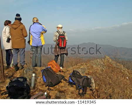 family of hiking people on the mountain top - stock photo