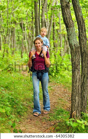 family of mother and baby walking in the forest