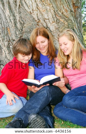Family of mother and children reading a book under a tree in summer park - stock photo
