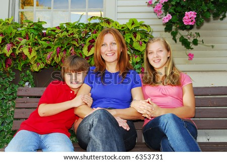 Family of mother and children sitting in front of their house - stock photo