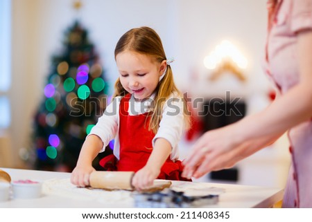 Family of mother and daughter baking Christmas gingerbread cookies at home on winter day - stock photo