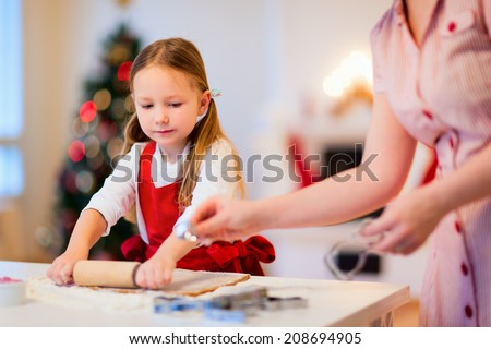 Family of mother and daughter baking gingerbread Christmas cookies at cozy home on winter day - stock photo