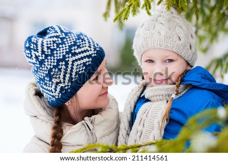 Family of mother and her adorable little daughter outdoors on beautiful winter day with snow - stock photo