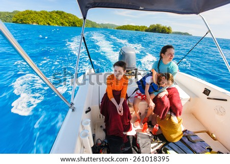 Family of mother and her kids at small boat on private water tour or excursion - stock photo