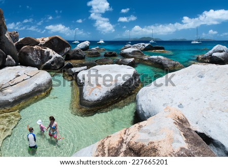 Family of mother and kids at The Baths beach area major tourist attraction at Virgin Gorda, British Virgin Islands, Caribbean - stock photo