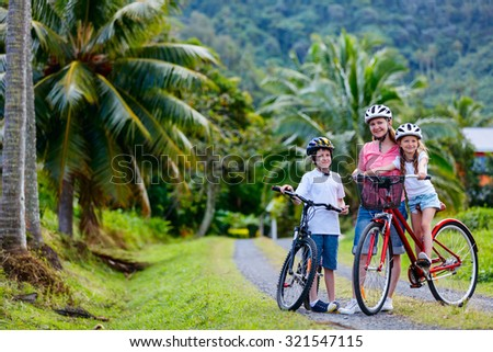 Family of mother and kids biking at tropical settings having fun together - stock photo