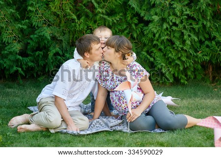 Family of mother father and boy, parent kissing at each other and little boy smiling and hugging. - stock photo