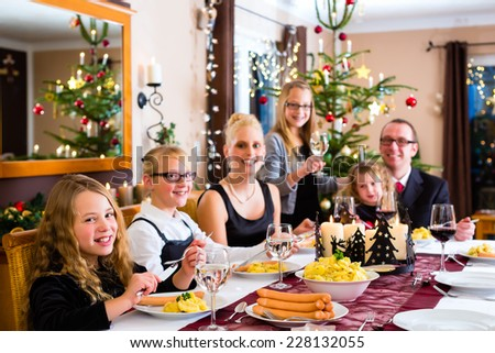 Family of Mother, father, children celebrating Christmas eve with traditional dinner Wiener sausages and potato salad  - stock photo