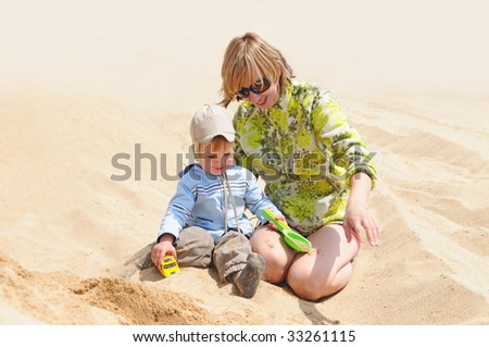 family of mother playing with kid on the sand sea beach