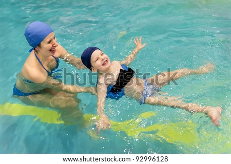 family of mother teaching kid in swimming pool - stock photo