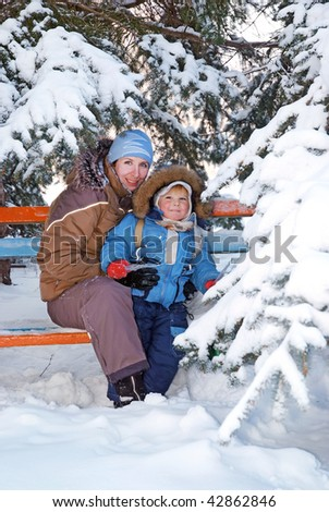 family of mother with kid under the snow fir tree