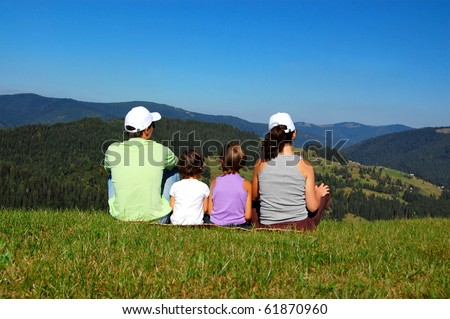 Family of parents and two kids looking at the beautiful view on their vacation - stock photo