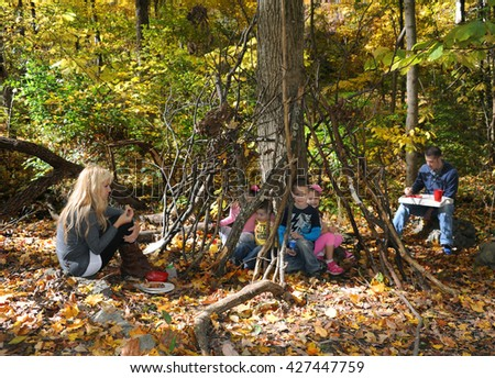 Family of six enjoy a rustic lunch as they camp in the Eastern part of Tennessee.  Woods, Autumn and colorful leaves surround them.  Kids are eating in their little house of sticks.