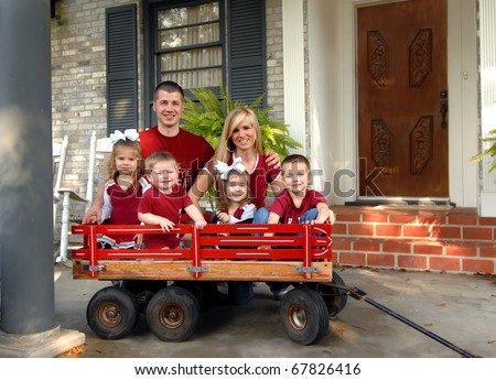 Family of six smile for a family photo.  They are all dressed in red and sitting on the front porch of their home.  Four kids are sitting in a red wooden wagon. - stock photo
