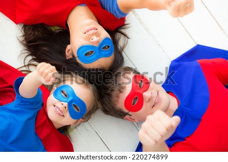 Family of superheroes lying on floor. Happy family having fun at home