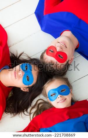 Family of superheroes lying on floor. Happy family having fun at home - stock photo