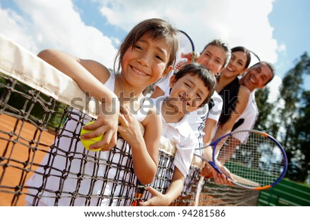 Family of tennis players at the court next to the net - stock photo