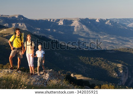 Family of thee people hiking at the mountains