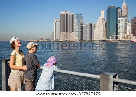 Family of three are standing on the quay at autumn day. - stock photo