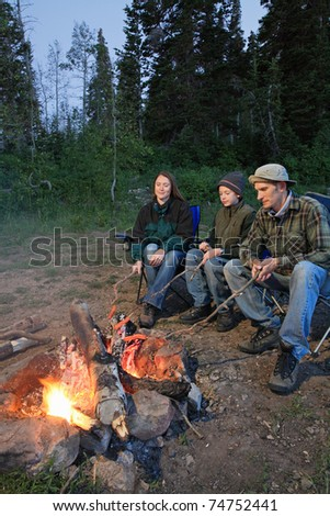 family of three camping and cooking hot dogs - stock photo