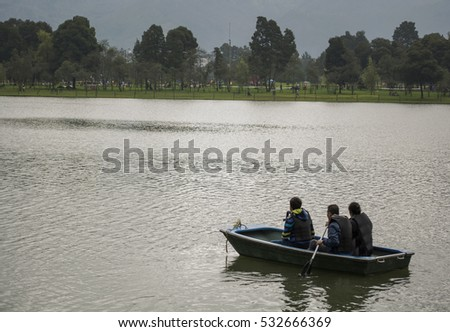 Family of three canoing on a calm river.