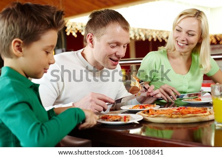 Family of three eating delicious pizza and enjoying themselves - stock photo