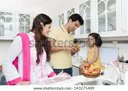 family of three eating fruits in the kitchen, Indian family in the kitchen, - stock photo