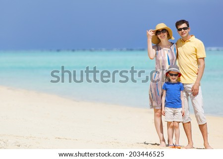 family of three enjoying their vacation at the beach - stock photo