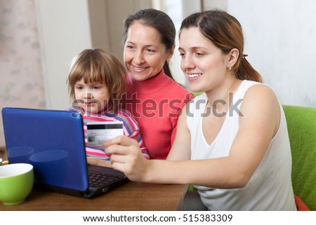 Family of three generations buying online with laptop and credit card at home