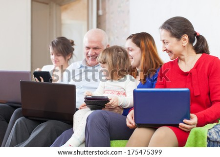 family of three generations on sofa in livingroom  with laptops  at home - stock photo