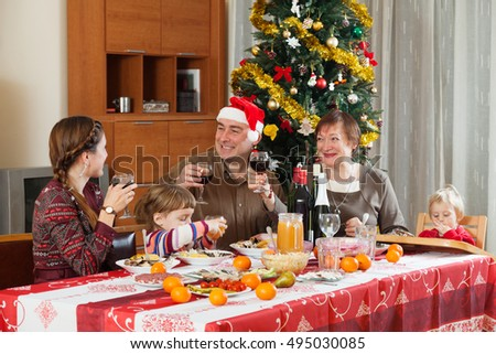 Family of three generations posing for Christmas portrait around festive table at home