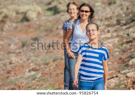 Family of three - girl, mother and grandmother hiking in the cross-country - stock photo