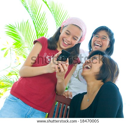 Family of three girls in fun expression laughing as they look at mobile phone - stock photo