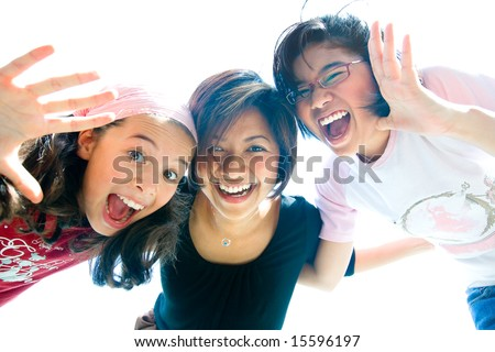 Family of three girls in fun expression playing together - stock photo