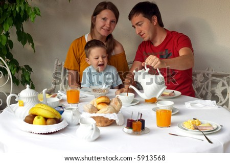Family of three having breakfast at terrace of theirs house - stock photo