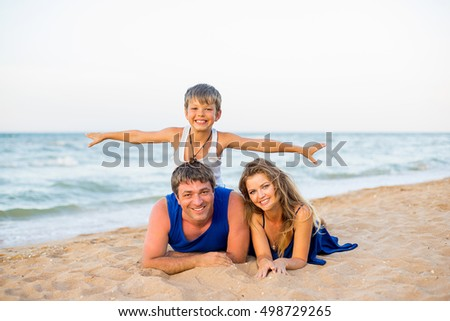 Family of three having fun at the beach, smiling and playing together