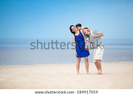 Family of three having fun on tropical beach during summer vacation - stock photo