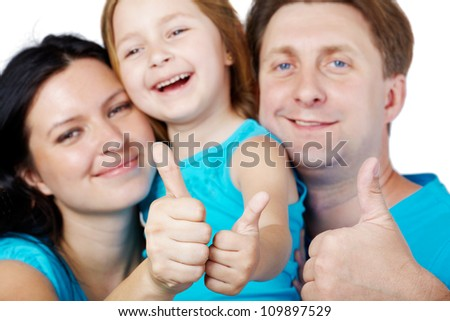 Family of three in blue shirts gives their thumbs up, focus on thumbs.